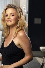 сексуальная Алисия Сильверстоун в черном вечернем платье улыбается и показывает грудь в декольте