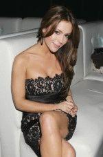 горячая красотка в откровенном платье сидит на белом диване
