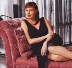 Наталья Бочкарева сидит на диване в платье с глубоким вырезом