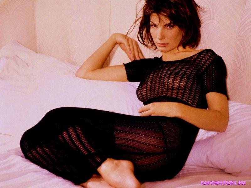сексуальная Сандра Буллок сидит на кровате в черном топике